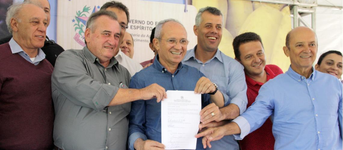 Prefeito Braz Delpupo e Governador Paulo Hartung seguram documento de entrega da escavadeira juntamente com outras autoridades - Ascom/PMVNI
